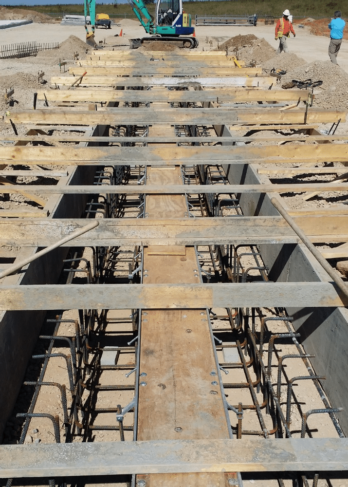 Plywood in top of trench drain is used to brace the channel drain.