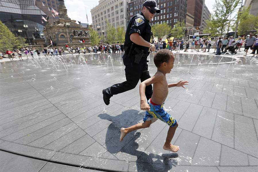 boy and police offer run near a water fountain on a slotted trench drain