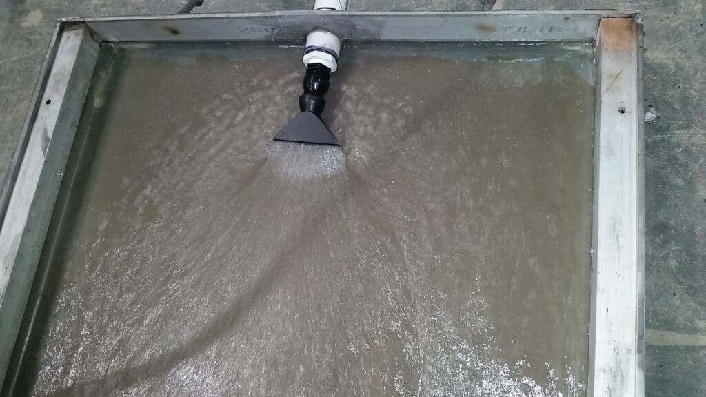 Trench drain flushing nozzle with fan patten