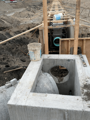 Trench drain outlet pipe connecting to structure